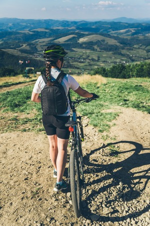 mtb: Young woman riding on MTB in mountains