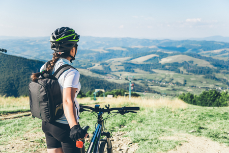 Young woman riding on MTB in mountains