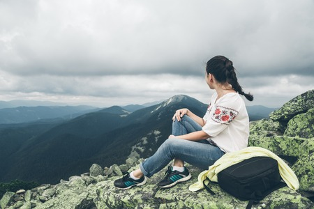 Young pretty woman in national ukrainian dress on the peak of the carpathian mountains Stock Photo