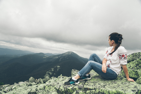 top veiw: Young pretty woman in national ukrainian dress on the peak of the carpathian mountains Stock Photo