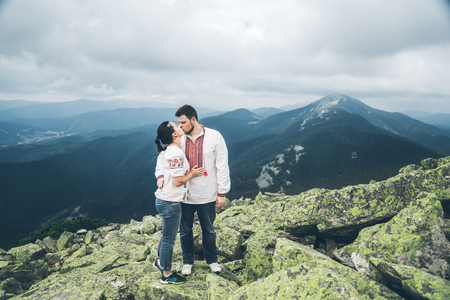 man and woman kissing each other on the top of the mountain Stock Photo