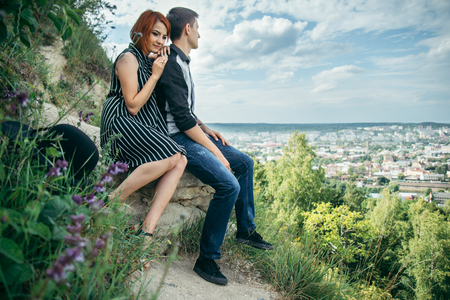 couple sitis on the hill with ponaramic view Stock Photo