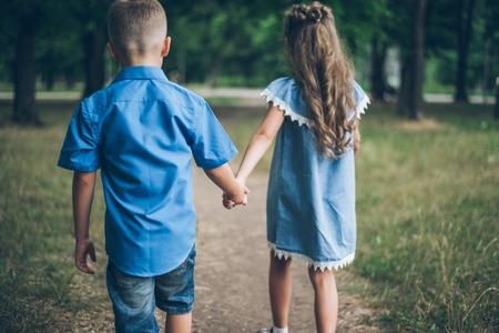 少しの男の子と女の子が一緒に歩いて、お互い手を取り合って