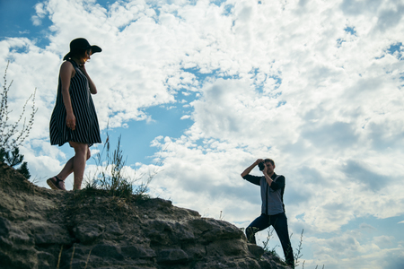 young couple on the hill, man taking picture of his girlfriend