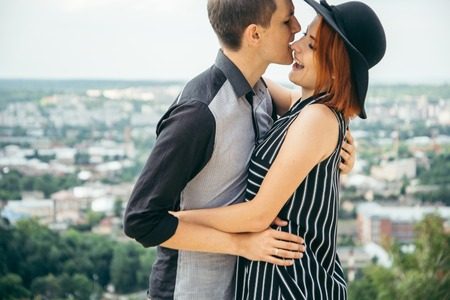 couple standing on the hill hugging and looking on city view