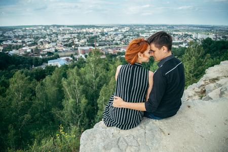 Junge Frau sitzt mit ihrem Freund auf dem Gipfel des Hügels Standard-Bild - 82870826