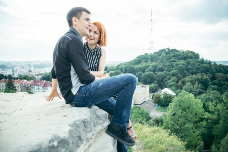 young woman sits with her boyfriend on the peak of the hill