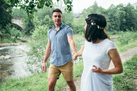 hapy: young pretty couple walking near mountains river