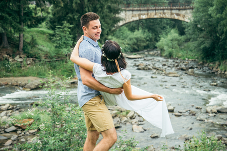 man taking woman on his arms near mountains river