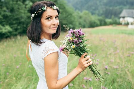 young pretty woman portrait with flowers in mountains Stock Photo