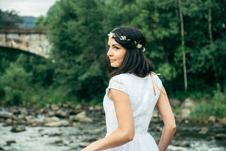 woman standing near mountains river in white dress and looking at the view