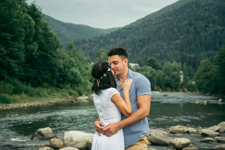 stands: couple stands near mountain river with mountains on background