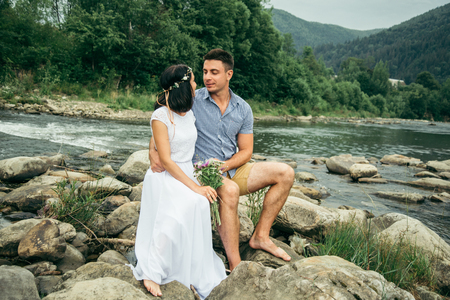 couple stands near mountain river with mountains on background