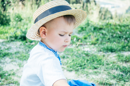 little boy sitting on the ground on the top of the mountains Stock Photo