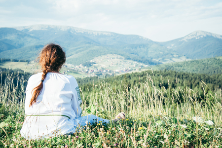 mature woman sitting on the peak of the hill and enjoing the view