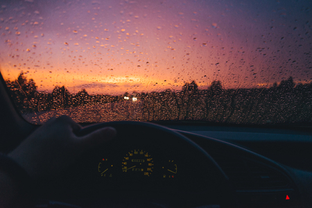 Rain drop on the car glass background with red sunset