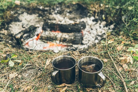 two metal cups with tea near bonfire Stock Photo