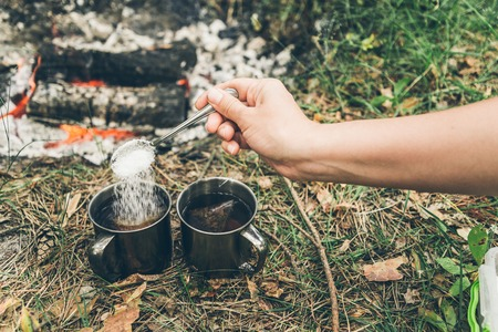 hand put suger in metal cup near bonfire