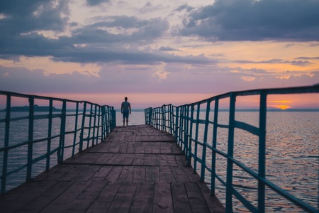 man standing on the pier and looking on sunset