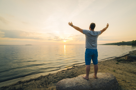 man on the beach looking on sunrise with hands up Stock Photo
