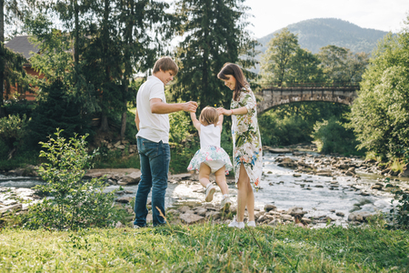 dauntless: happy family play with daughter near the river in mountains Stock Photo
