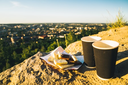 two cups of coffee on the peak of the hill