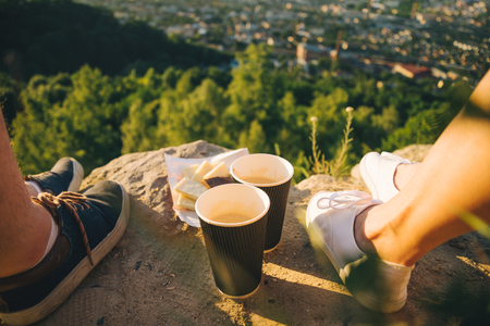 man and woman legs on the top of the hill with two cups and chocolate Stock Photo