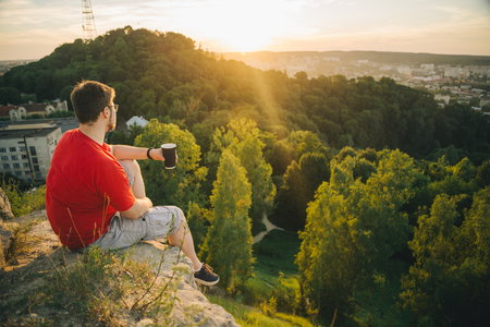 man sitting on the top of the hill with cup of coffee and watching sunset over the city