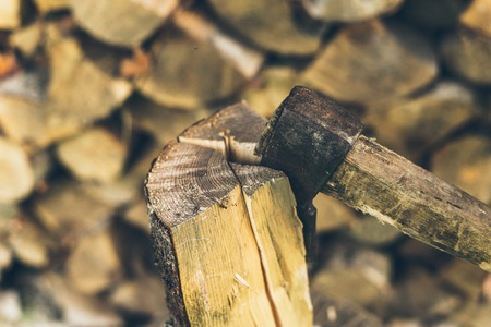 filings: axe in log on a firewood background