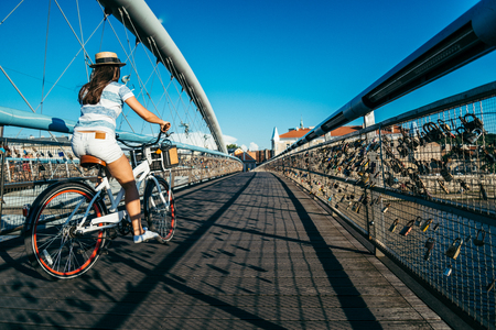 pretty woman riding bicycle on the bridge