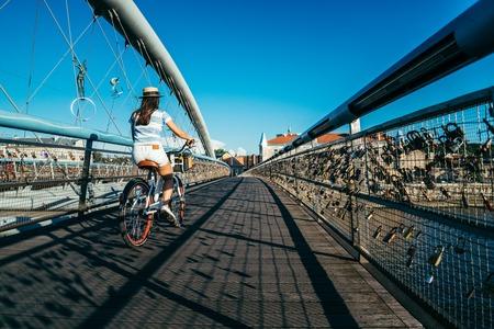 kick around: pretty woman riding bicycle on the bridge