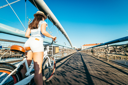 the furlough: woman stands with bicycle in the middle of the bridge