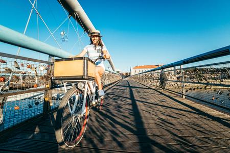 the furlough: pretty woman riding bicycle on the bridge