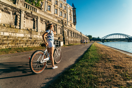 the furlough: pretty woman ride bicycle on embankment of Wisla river