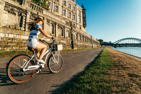 kick around: pretty woman ride bicycle on embankment of Wisla river