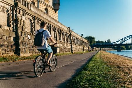 the furlough: man riding bicycle at embankment at the sunset
