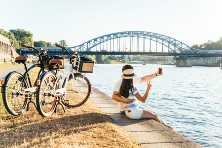 couple sitting at the embankment and taking selfie