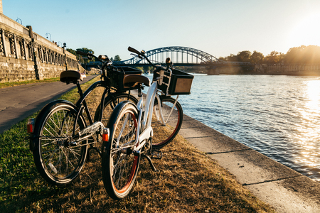 kick around: two bicycles at the embankment on sunset