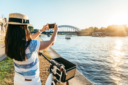 kick around: woman taking picture of the river at embankment on sunset