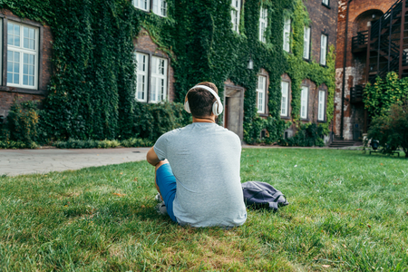 the furlough: man sitting on the ground in city park and looking on old building