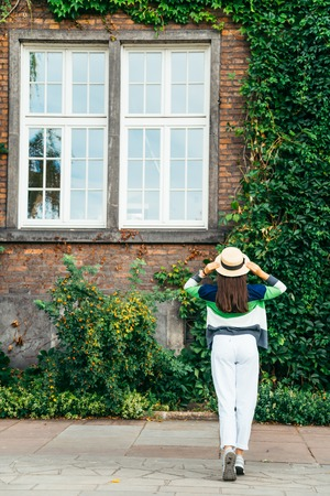 woman stands in front of old building in ivy Stock Photo