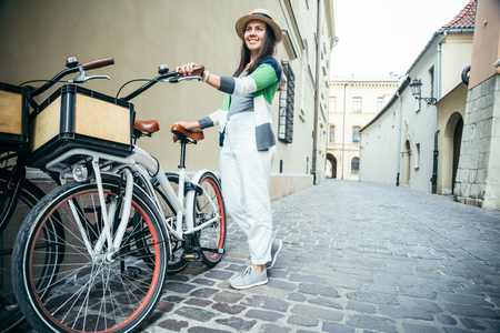 the furlough: woman stading near bicycle that parked in old narrow european street