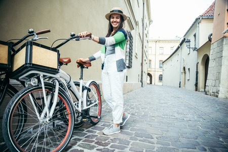 kick around: woman stading near bicycle that parked in old narrow european street