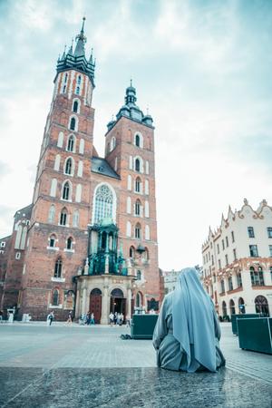 nun looking on old church Stock Photo