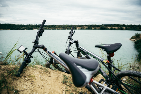 kick around: two bicycles on the riverside with beautiful view of water on background
