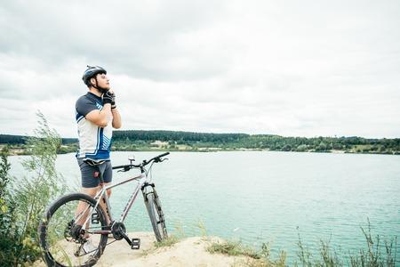 自転車やチェックのヘルメットが付いている湖近くに立っている近くの男 写真素材