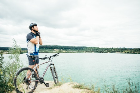 man near standing near lake with bicycle and check helmet