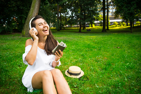 woman in the park happy to use powerbank and continue listen music