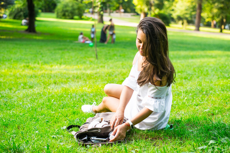 woman get water from backpack while resting in park Stock Photo