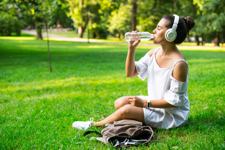 the furlough: woman get water from backpack while resting in park Stock Photo
